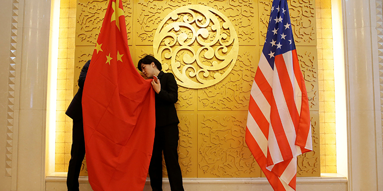 Staff members set up Chinese and U.S. flags for a meeting between Chinese Transport Minister Li Xiaopeng and U.S. Secretary of Transportation Elaine Chao at the Ministry of Transport of China in Beijing on April 27, 2018.