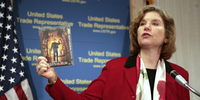 U.S. Trade Representative Susan Schwab holds up a pirated DVD as she talks about two WTO cases against China during a news conference in Washington, DC, on April 9, 2007.