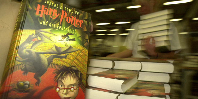 A woman piles up copies of the German translation of Harry Potter and the Goblet of Fire in a warehouse in Bad Hersfeld near Kassel, Germany, on October 12, 2000.