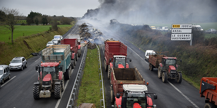 French farmers take part in a blockade on a motorway near Arzal, western France, on January 29, 2016, during a protest against the falling of prices of their products.
