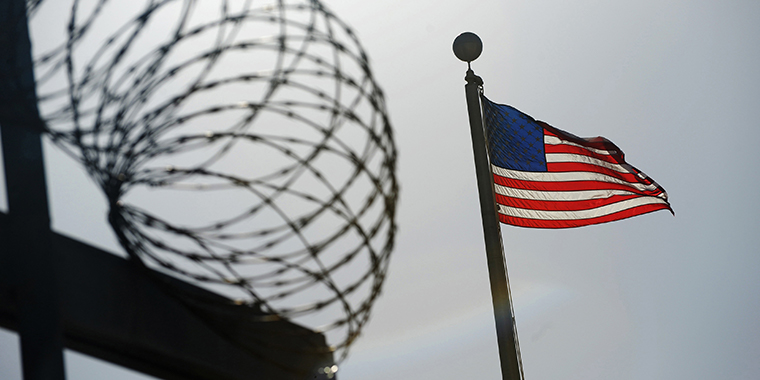 "A U.S. flag flies above a razor wire-topped fence at the ""Camp Six"" detention facility at the U.S. Naval Station at Guantanamo Bay on December 10, 2008."