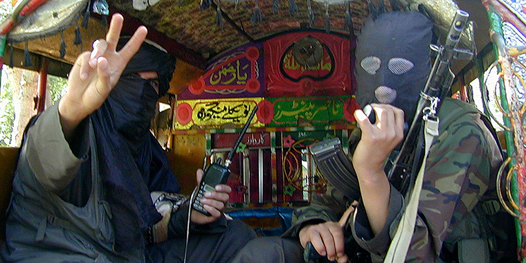 Pakistani Taliban fighters gesture towards the camera before leaving Buner, about 100 km (60 miles) northwest of Islamabad, Pakistan in 2009.