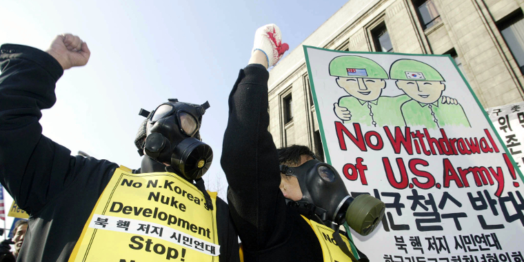 South Korean protesters in gas masks shout anti-North Korean slogans during a rally in Seoul on January 11, 2003, a day after North Korea withdrew from the Treaty on the Nonproliferation of Nuclear Weapons.