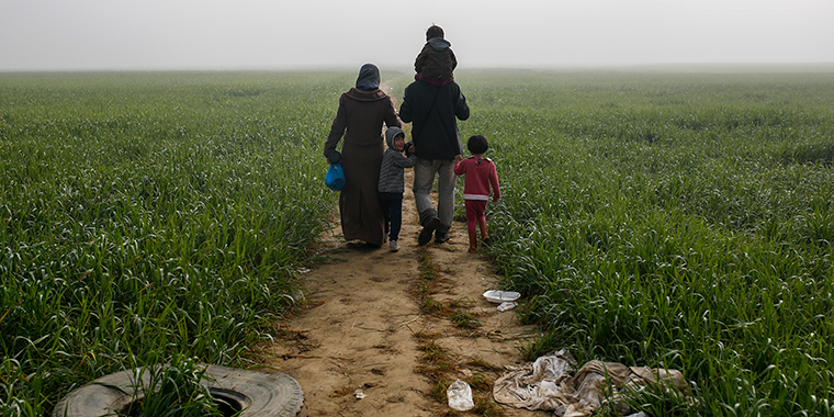 A family walks through a field at a makeshift camp for migrants and refugees at the Greek-Macedonian border near the village of Idomeni, Greece, on April 4, 2016.