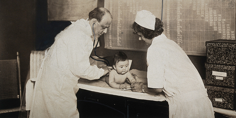 A baby is examined by a nurse and a doctor with a stethoscope at a state baby clinic in Pennsylvania, circa 1925.