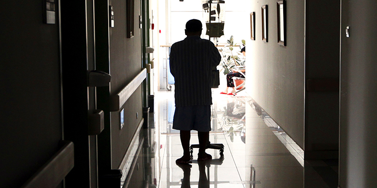 A cancer patient pushes his drip stand as he walks down the hallway of the Beijing Cancer Hospital on July 12, 2011.