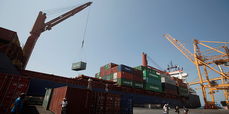 A ship uses its crane to unload containers at a  terminal at the Red Sea port of Hodeidah, Yemen on November 16, 2016.